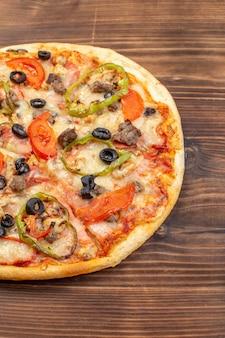 茶色の木の表面においしいチーズピザを正面から見る