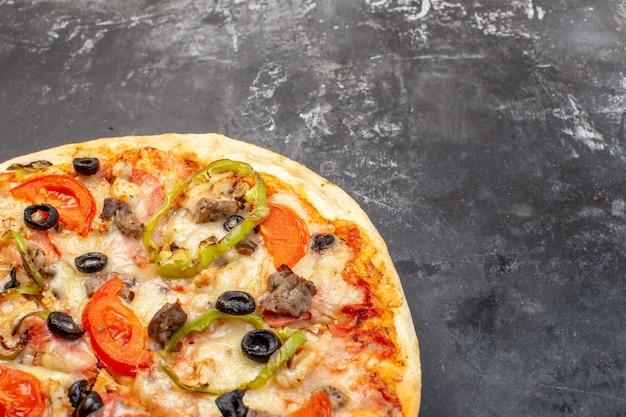 灰色の表面においしいチーズピザを正面から見る