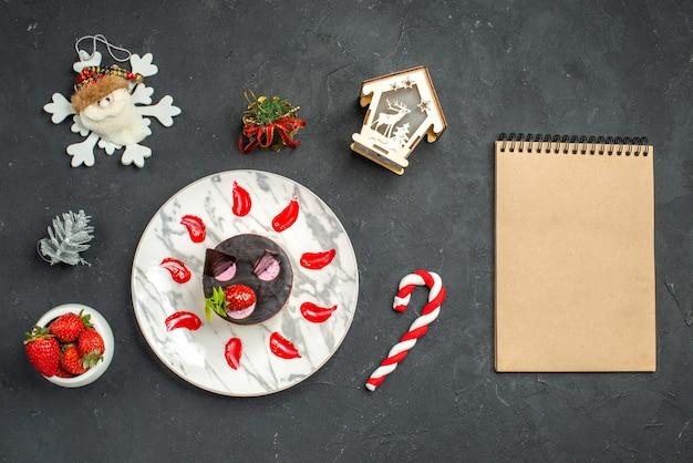 暗い背景の上のイチゴクリスマスツリーおもちゃノートブックの楕円形のプレートボウルにイチゴとチョコレートの正面図おいしいチーズケーキ
