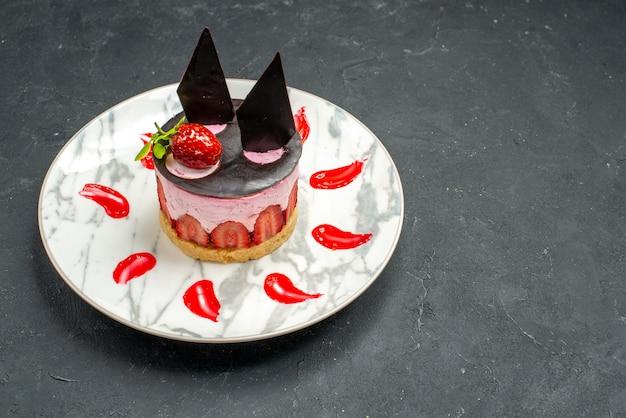 正面から見ると、イチゴとチョコレートが入ったおいしいチーズケーキが、空きスペースのある暗い場所にある楕円形のプレートに置かれています。