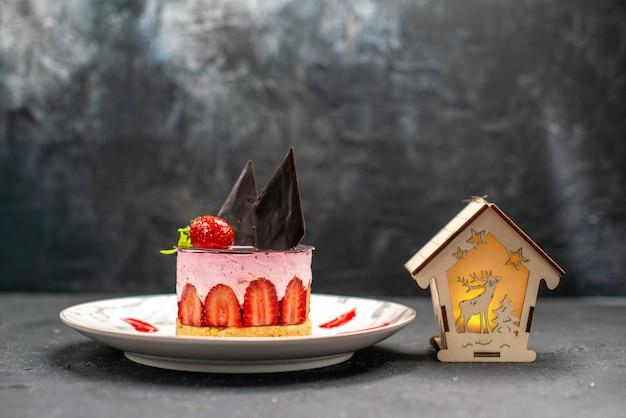 正面図楕円形のプレートにイチゴとチョコレートのおいしいチーズケーキ暗い上のクリスマスランタン