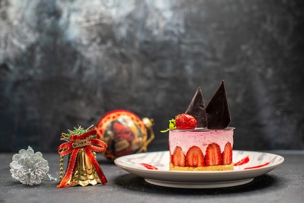 暗い自由空間の楕円形のプレートクリスマスツリーのおもちゃにイチゴとチョコレートの正面図おいしいチーズケーキ