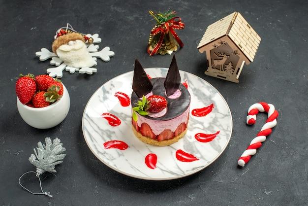 Вид спереди вкусный чизкейк с клубникой и шоколадом на тарелке, миске с игрушками из клубники на рождественской елке на темном фоне