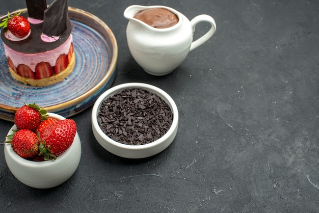 正面図チョコレートイチゴとプレートボウルにイチゴとチョコレートのおいしいチーズケーキ暗い孤立した背景の無料の場所にダークチョコレート