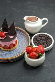 어두운 외진 배경에 초콜릿 딸기 다크 초콜릿이 있는 접시 그릇에 딸기와 초콜릿을 곁들인 맛있는 치즈 케이크 전면 보기