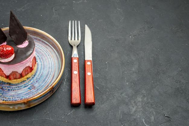Вид спереди вкусный чизкейк с клубникой и шоколадом на тарелке, вилке и ноже на темноте