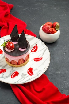 Вид спереди вкусный чизкейк с клубникой и шоколадом на тарелке, миска из красной шали с клубникой на темном изолированном фоне