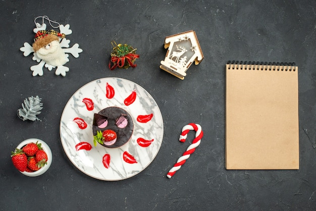 Front view delicious cheesecake with strawberry and chocolate on oval plate bowl of strawberries xmas tree toys notebook on dark background