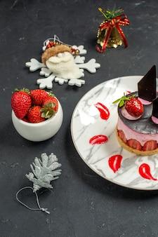 Vista frontale deliziosa cheesecake con fragole e cioccolato su piatto ovale ciotola di fragole
