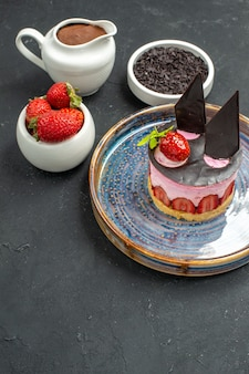 Front view delicious cheesecake with strawberry and chocolate on oval plate bowls with strawberries chocolate on dark