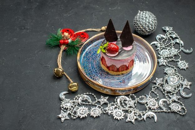Vista frontale deliziosa cheesecake con fragole e cioccolato su piatto ovale ornamento di natale su un posto libero al buio