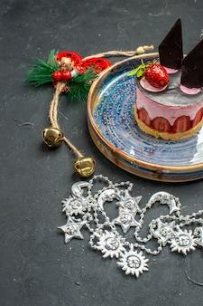 Vista frontale deliziosa cheesecake con fragole e cioccolato su ornamenti di natale piatto ovale su oscurità