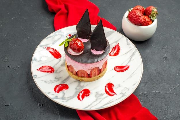 Vista frontale deliziosa cheesecake con fragole e cioccolato su piatto scialle rosso ciotola con fragole su oscurità
