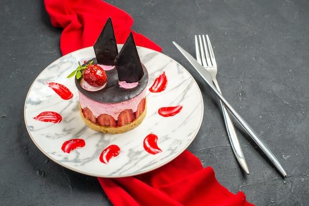 Vista frontale deliziosa cheesecake con fragole e cioccolato su piatto scialle rosso incrociato coltello e forchetta sul buio