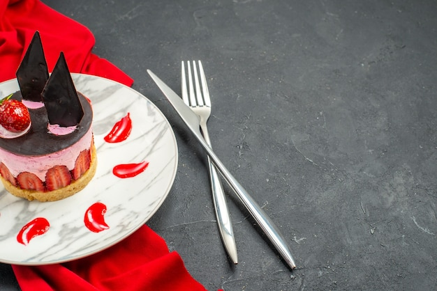 Front view delicious cheesecake with strawberry and chocolate on plate red shawl crossed knife