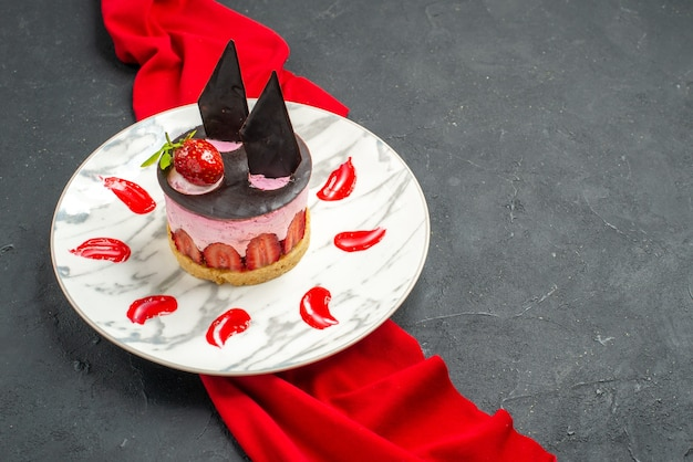 Front view delicious cheesecake with strawberry and chocolate on plate red shawl on dark isolated background free place