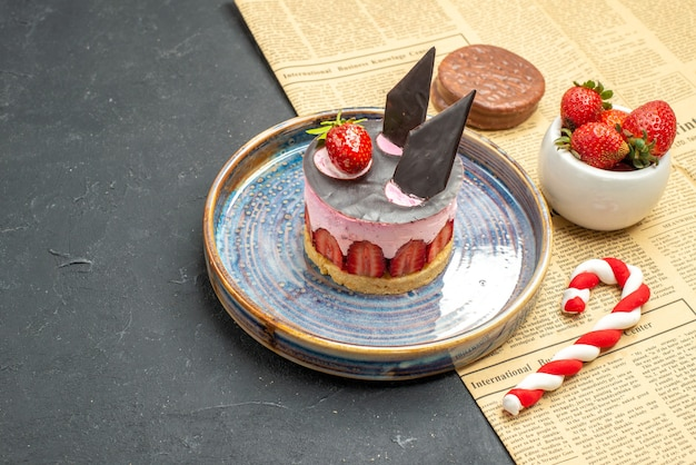 Front view delicious cheesecake with strawberry and chocolate on plate strawberry bowl biscuit xmas candy