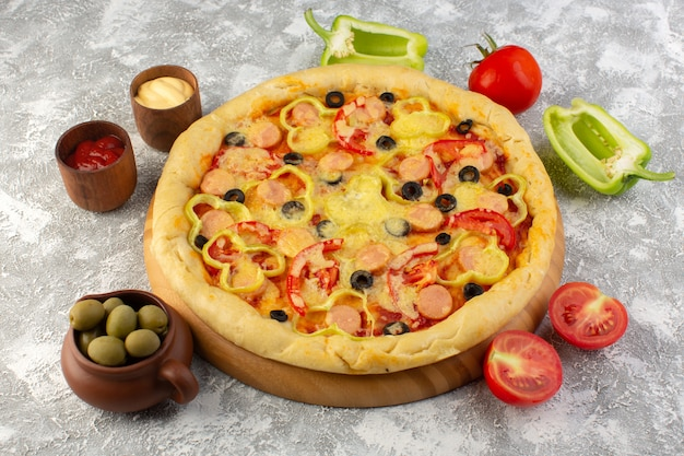 Front view of delicious cheesy pizza with olives sausages and tomatoes