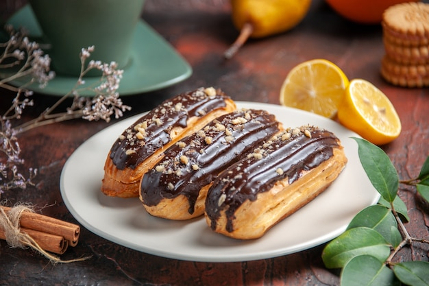 Front view delicious choco eclairs on the dark background