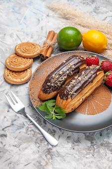 Front view delicious choco eclairs with cookies on light table dessert cake cookie