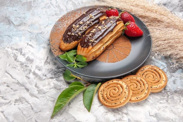Front view delicious choco eclairs with cookies on white table cake biscuit dessert