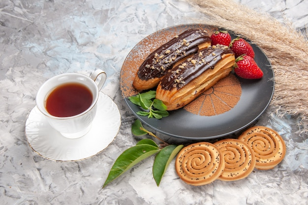 Front view delicious choco eclairs with cup of tea on white table cake biscuit dessert