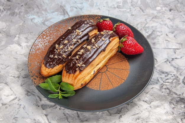 Front view delicious choco eclairs with strawberries on light table cake dessert cookie