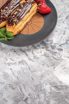 Vista frontale deliziosi bignè al cioccolato con fragole su biscotti da dessert con torta da tavola leggera