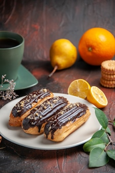 Front view delicious choco eclairs with tea on a dark background