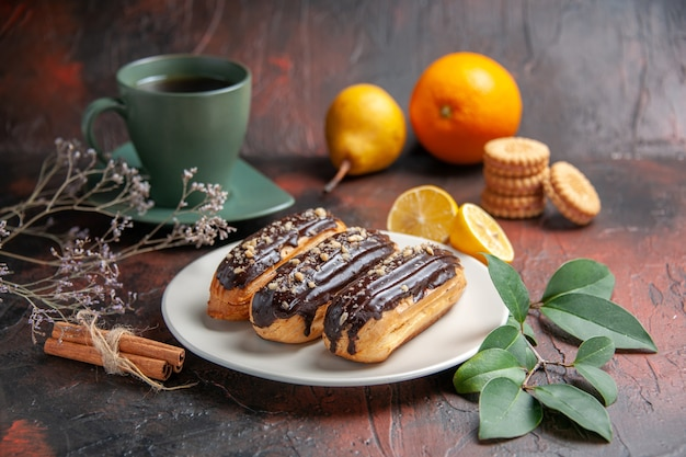 Front view delicious choco eclairs with tea on dark background