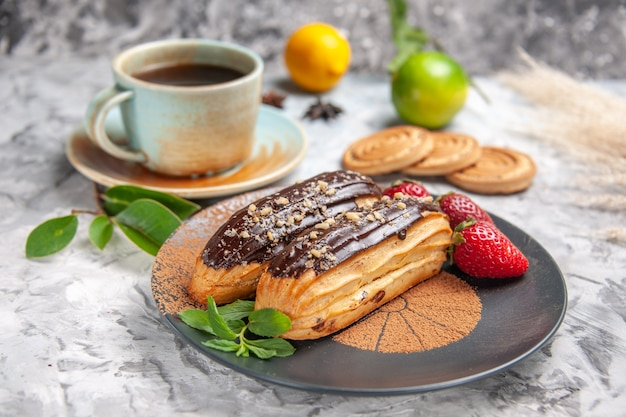 Front view delicious choco eclairs with tea on white table cookie dessert cake