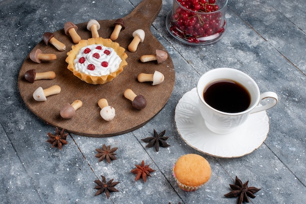 正面の新鮮な赤いクランベリーケーキと灰色の素朴な机の上のコーヒーカップのおいしいチョコレートビスケット