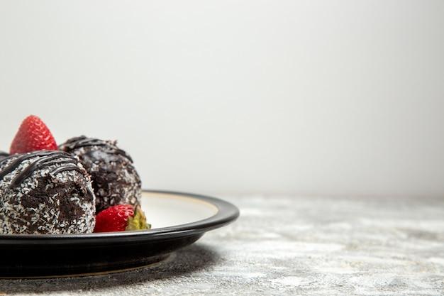 正面図薄白の表面に新鮮な赤いイチゴが入ったおいしいチョコレートケーキチョコレートシュガービスケットの甘いケーキ焼き