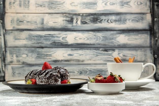 Vista frontale deliziose torte al cioccolato con fragole fresche sulla superficie bianca biscotto zucchero al cioccolato dolce cuocere il biscotto