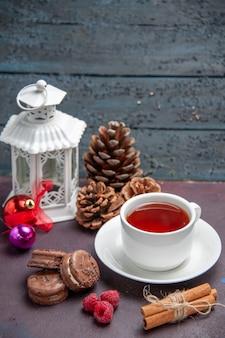 暗い背景の上のお茶とおいしいチョコレートクッキーの正面図パイビスケット甘いティーケーキクッキー
