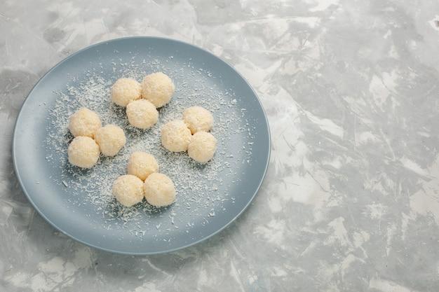 Vista frontale di deliziose caramelle al cocco all'interno del piatto blu sul muro bianco
