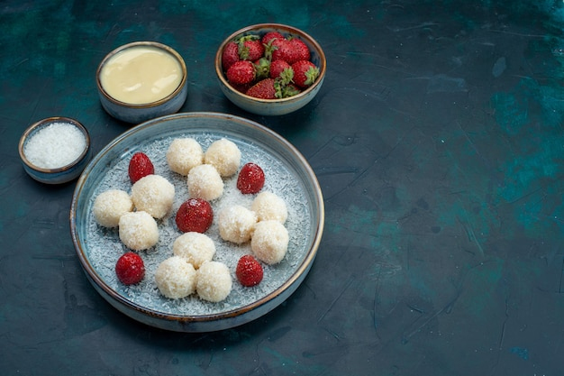 Vista frontale di deliziose caramelle al cocco con fragole