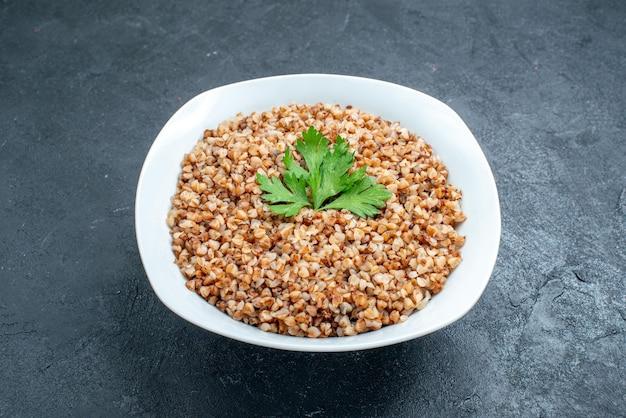 Vista frontale delizioso pasto utile di grano saraceno cotto all'interno del piatto sullo spazio buio