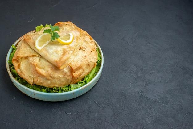 어두운 표면에 채소와 레몬 접시 안에 전면보기 맛있는 요리 피타