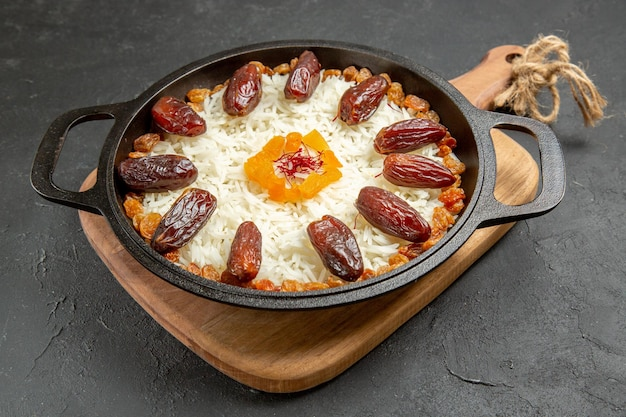 Front view delicious cooked plov rice meal with khurma and raisins on grey surface plov rice cooking dish meal