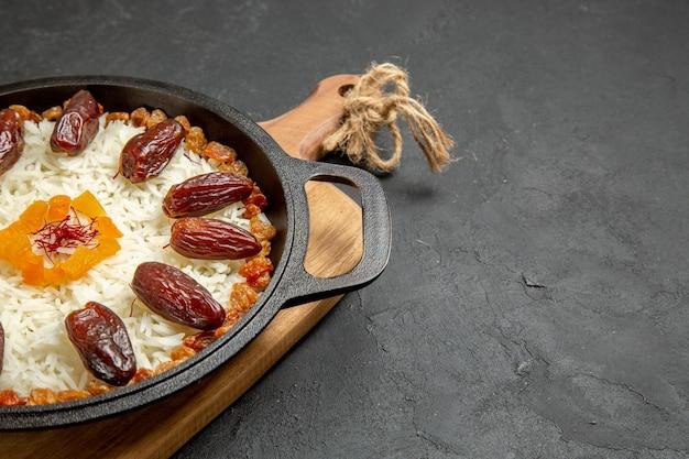 Vista frontale deliziosa farina di riso plov cotta con khurma e uvetta sulla superficie grigia cottura del piatto di riso plov