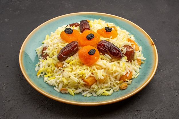 Front view delicious cooked plov rice with different raisins inside plate on grey space
