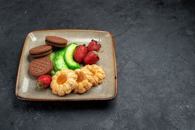 Front view delicious cookies chocolate and simple ones with fresh red strawberries on dark grey wall sugar biscuit cake sweet cookie
