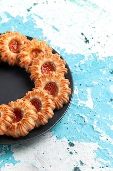 Вид спереди восхитительное печенье круглой формы с джемом внутри черной тарелки на синей стене печенье сахарный сладкий бисквитный торт