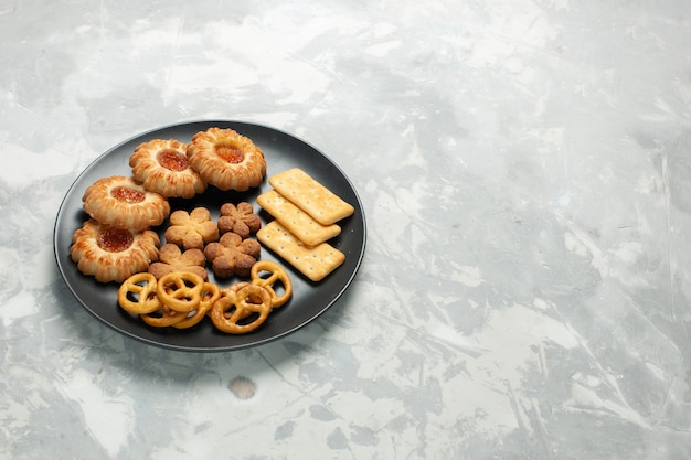Front view delicious cookies with crackers and crisps inside plate on light white desk