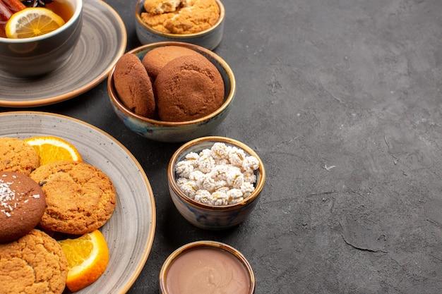 Вид спереди вкусное печенье с чашкой чая и нарезанными апельсинами на темном фоне, печенье, фрукты, сладкий торт, печенье, цитрусовые