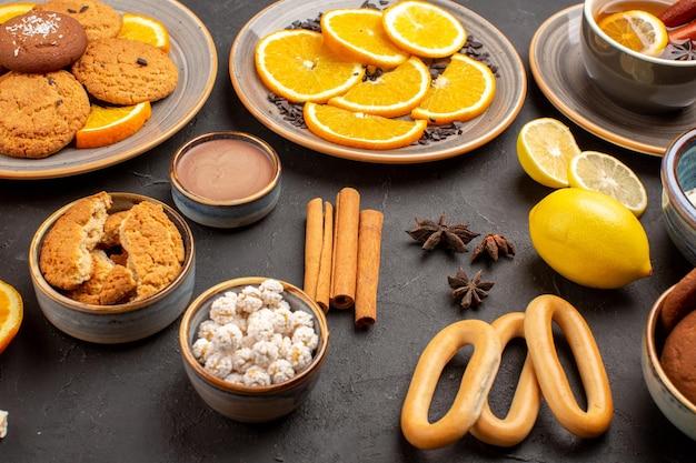 Вид спереди вкусное печенье со свежими апельсинами и чаем на темном фоне сахарное печенье фруктовое печенье сладкое