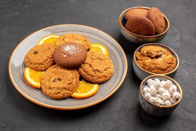 Vista frontale deliziosi biscotti con arance fresche affettate sullo sfondo scuro biscotti torta frutta dolce biscotto agli agrumi