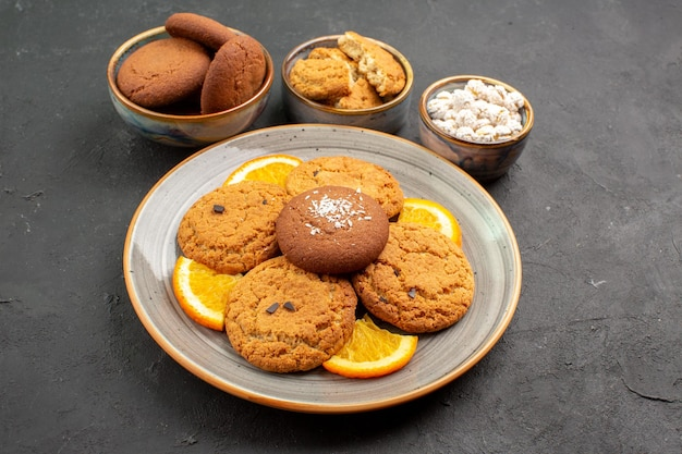 Front view delicious cookies with fresh sliced oranges on dark background fruit cookie cake citrus biscuit sweet