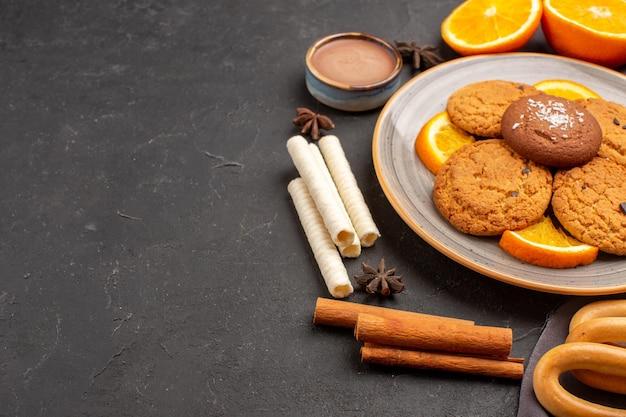 正面図ダークデスクに新鮮なスライスしたオレンジとおいしいクッキーシュガークッキーフルーツビスケット甘い